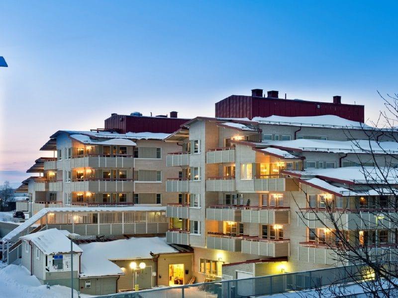 Lägenhetshus i fyra våningsplan med ljust tegel och rött tak.