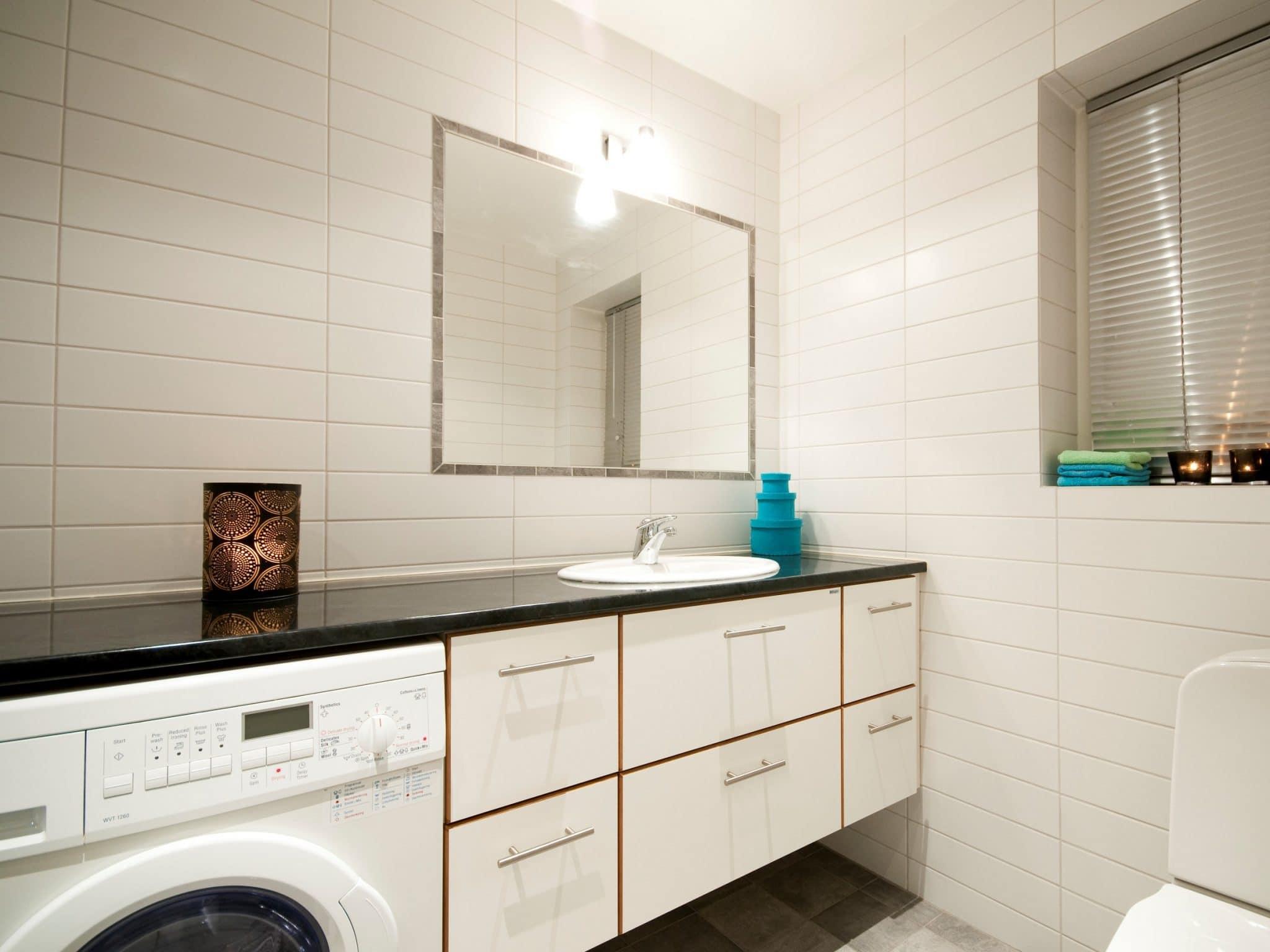 Ljust, kaklat badrum med tvättmaskin i Olympia 1 i Åre