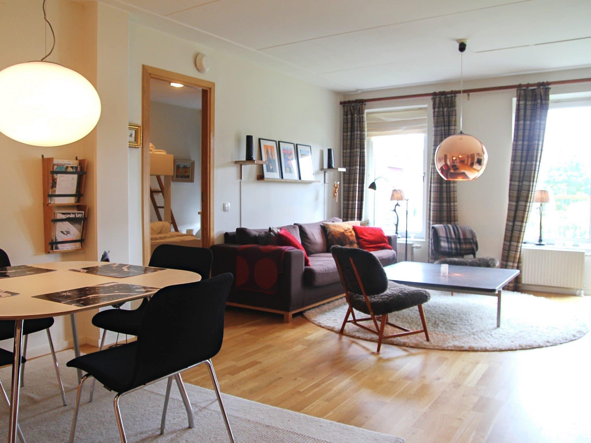 Vardagsrum i Åreparken i Åre med svart soffa och kopparlampa