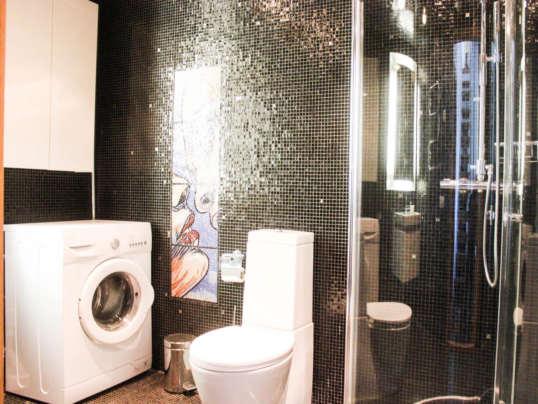 Badrum i Åreparken i Åre med svart kakel, dusch och tvättmaskin