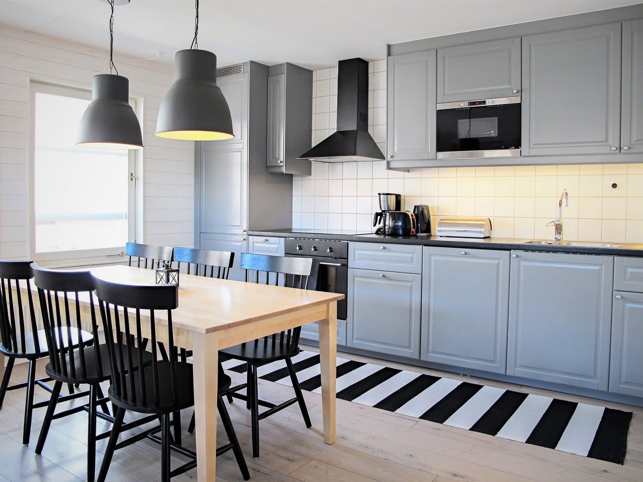 Kök i modern stil med spishäll, inbyggd ugn och skåpluckor i grå nyans.